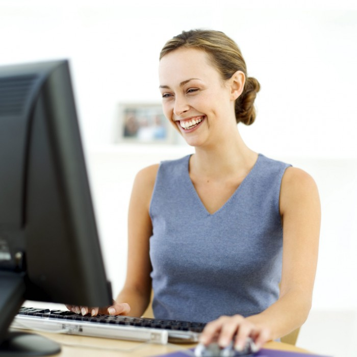 Young Woman Sitting in Front of a Computer and Laughing